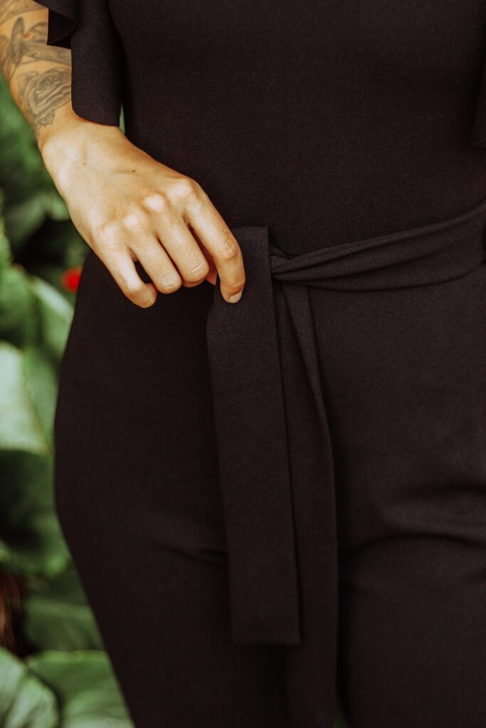 Dressed up for party in a black jumpsuit with frill sleeves from femme luxe finery.