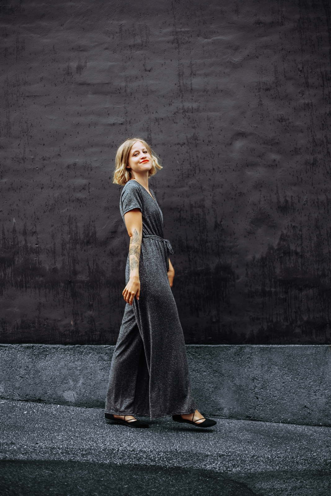 Dressed up for party in a black glitter jumpsuit from femme luxe finery.