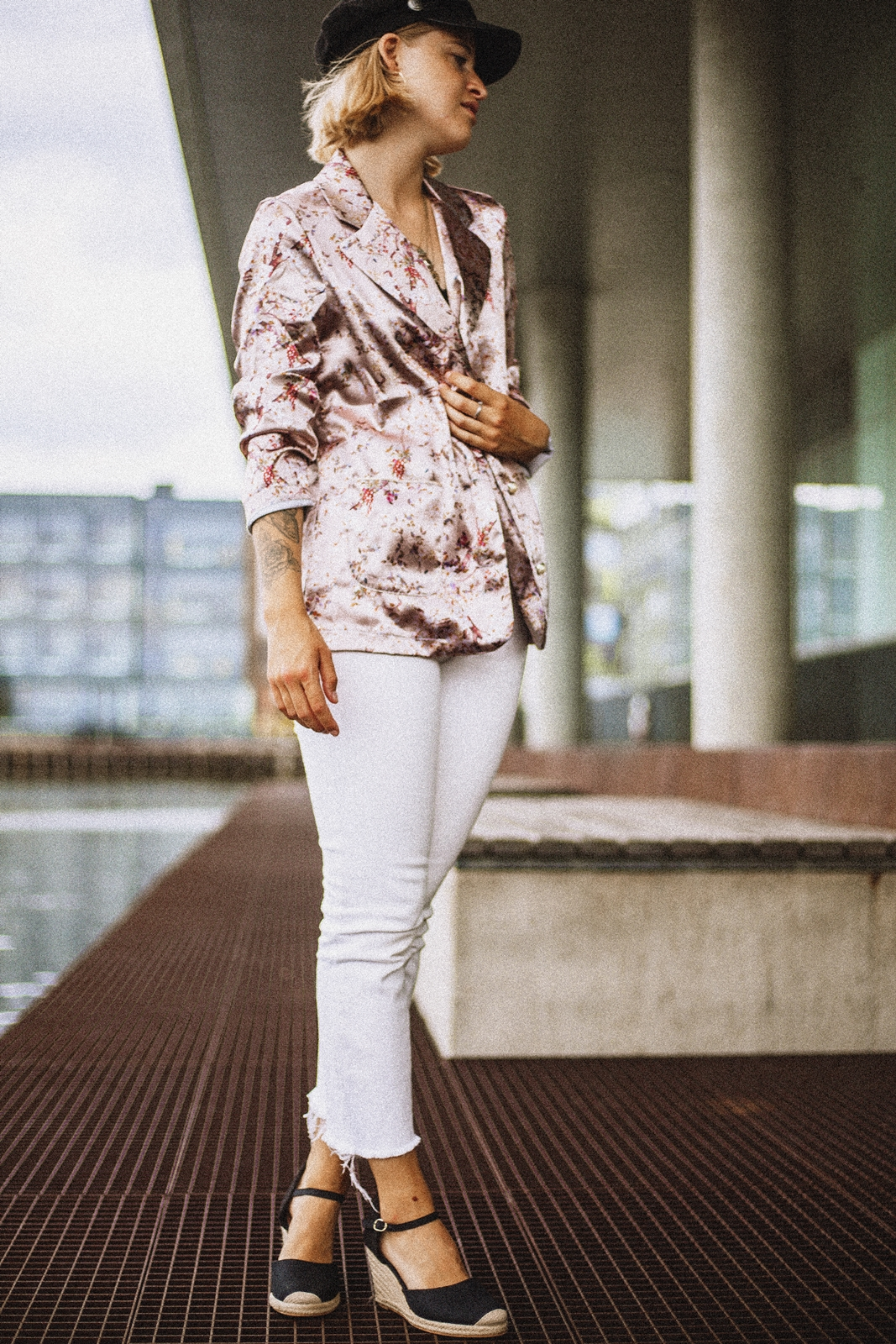floral satin blazer styled with bakerboy hat and layered pendant necklace and earrings and also white jeans and summer wedges