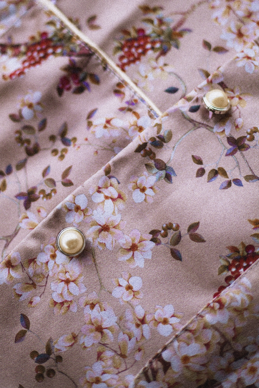 flat closeup look of floral satin blazer with pearl buttons