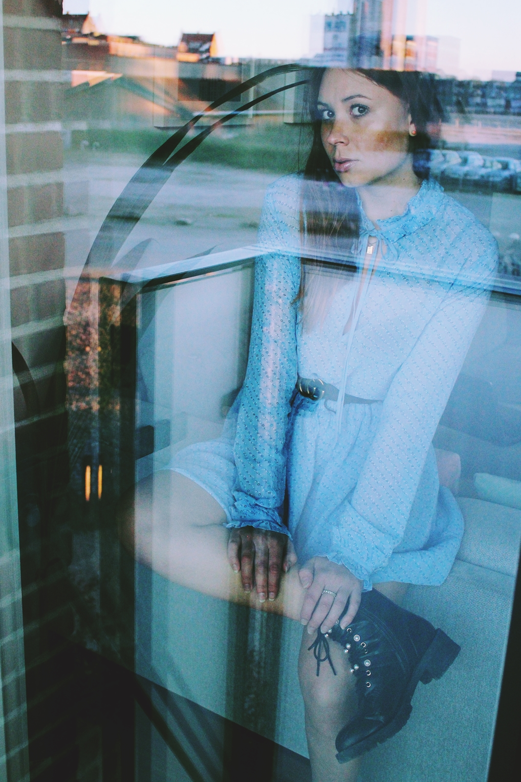 shot through window wearing blue dress and combat boots