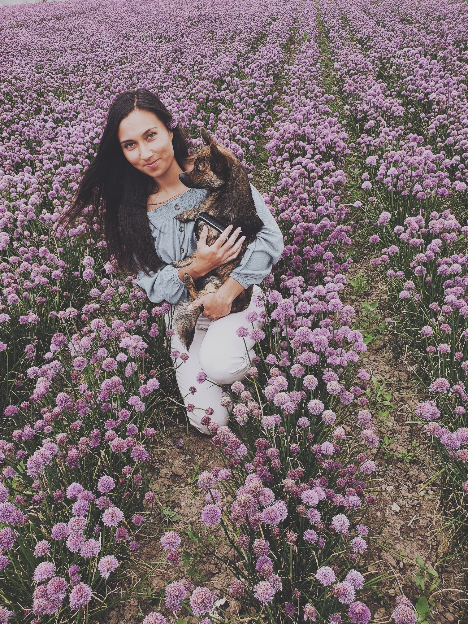 my friend sitting with her dog in a flower field